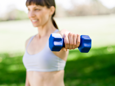 Portrait of cheerful woman in fitness wear exercising with dumbbell Reklamní fotografie - 89917577