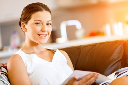 Happy woman reading a magazine sitting on a sofa