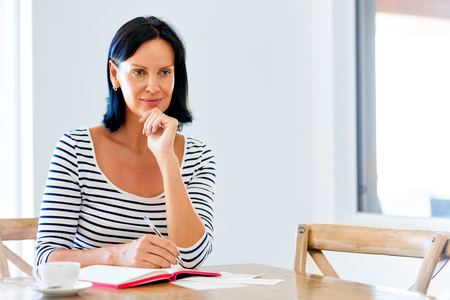Pretty woman writing in an agenda at home or office