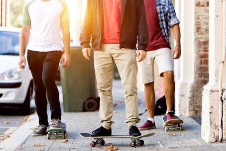 Tienervrienden die bij de straat met skateboards lopen