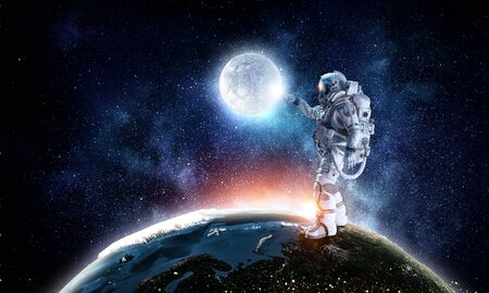 Astronaut pointing with finger on moon planet.