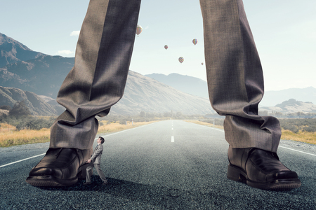 Feet of giant businessman standing on road. Mixed media