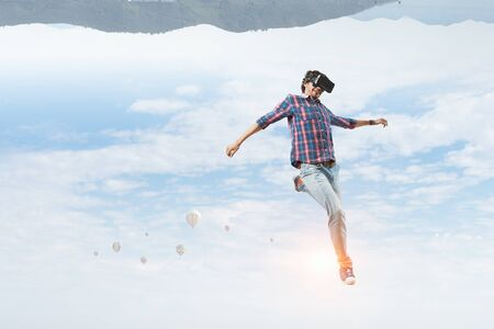 Young man in checked shirt and headset experiencing virtual reality. Mixed media