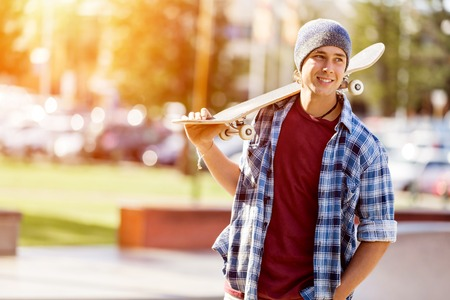 Teenage boy with skateboard standing outdoors