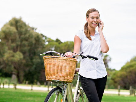 Beautiful young blonde woman with bike in park talking over phone