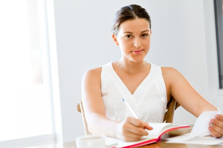 Young woman writing in an agenda at home or office