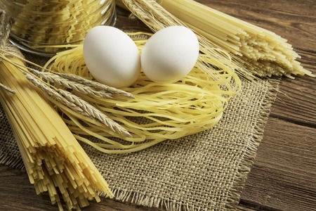 Dry spaghetti pasta and eggs on table ready for cooking