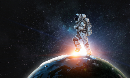 Astronaut in space suit running on Earth planet surface. Фото со стока