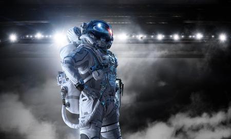 Astronaut wearing space suit in dark interior. Mixed media
