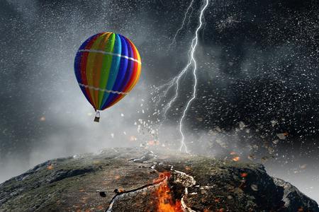 Color aerostat flying in sky above crack in ground
