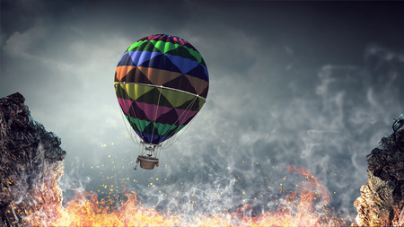 Colorful aerostat flying in dark sky above fire flames