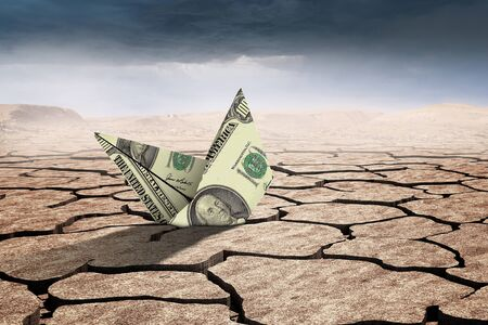 Dollar banknote ship in desert as symbol for financial crisis