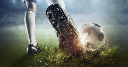 Foot of soccer player kicking ball. Mixed media Banque d'images