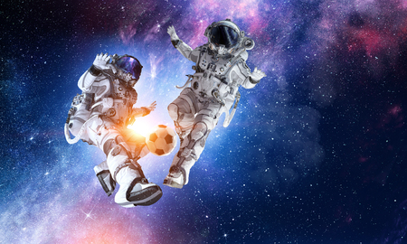 Two astronauts floating in open space and fighting for ball. Mixed media Stock Photo