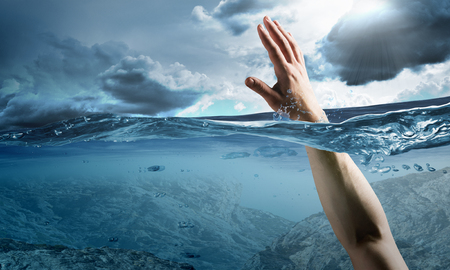Man drowning in sea and asking for hand of help