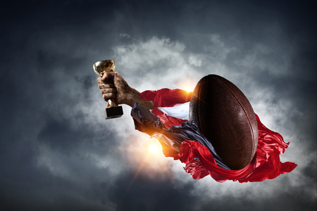 Hand of winner tighten the cup against sky background Stok Fotoğraf