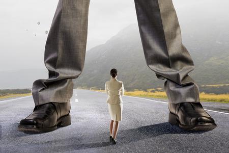 kleine zakenvrouw en benen van gigantische baas. Gemengde media