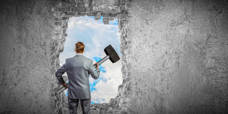 Businessman with hammer and hole in stone wall. Mixed media Stock Photo