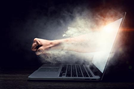 男性の拳は、ノート パソコンの画面から来ています。ミクスト メディア 写真素材
