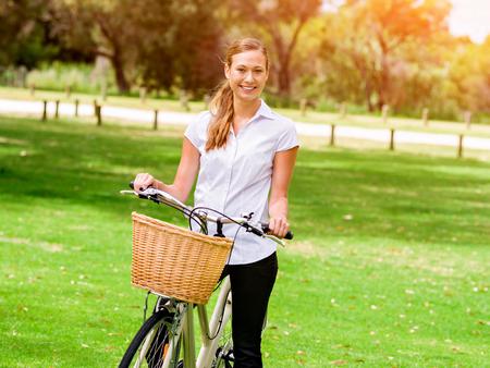公園では自転車の若いブロンド美女 写真素材