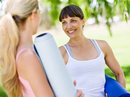 Two young women with a gym mat chatting in the park
