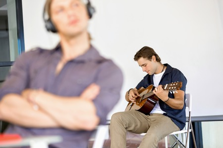 Young man playing the guitar in office Reklamní fotografie