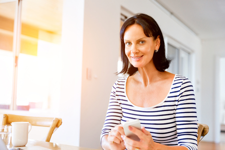 Portrait of attractive woman holding phone