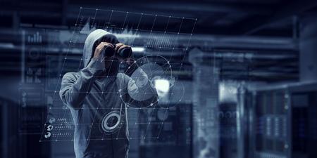Unrecognizable man wearing hoody looking in to binoculars. Mixed media 版權商用圖片