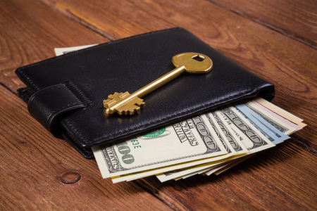 Dollar banknotes in leather purse and golden key on wooden table