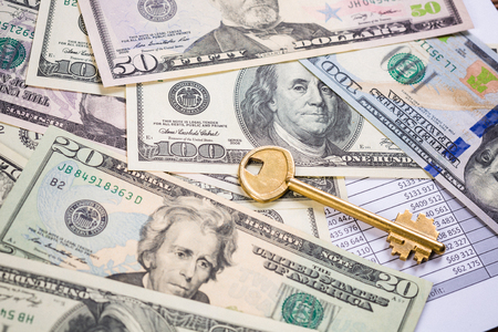 Golden key on top of US dollar bills Stock Photo