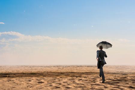 Businessman in suit with black umbrella running in desert