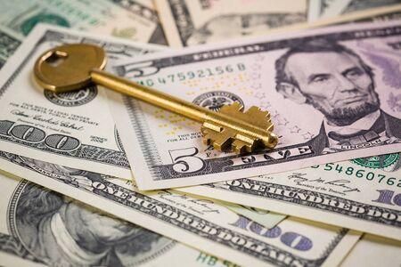 Golden key on top of US dollar bills Stock Photo