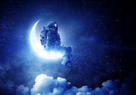Spaceman sitting on moon against dark starry sky. Mixed media