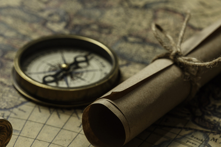Old map compass and roll on table