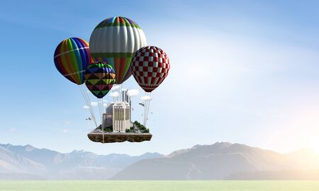 Mini city exterior flying high in sky on aerostats. Mixed media Stock Photo