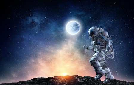 Astronaut in space suit running on planet surface. Mixed media Stockfoto