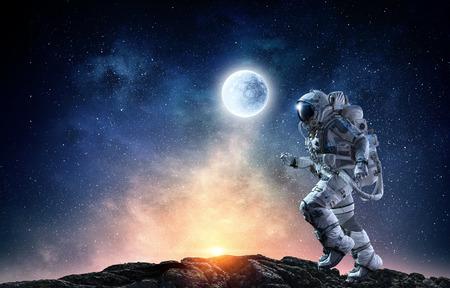 Astronauta w skafandrze na powierzchni planety. Różne środki przekazu