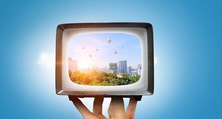 昔ながらの人間の手のひらに管テレビ。ミクスト メディア