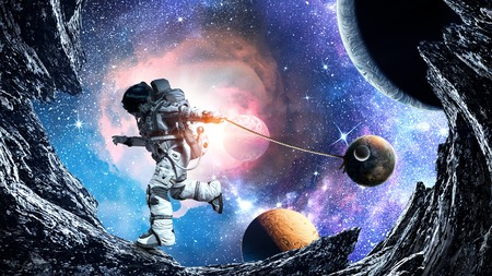 Fantasy image with spaceman catch planet. Mixed media Foto de archivo