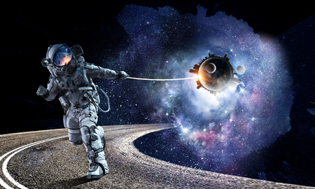 Fantasy image with spaceman catch planet. Mixed media Banco de Imagens