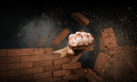 Hand breaking through the wall. Mixed media Stock Photo