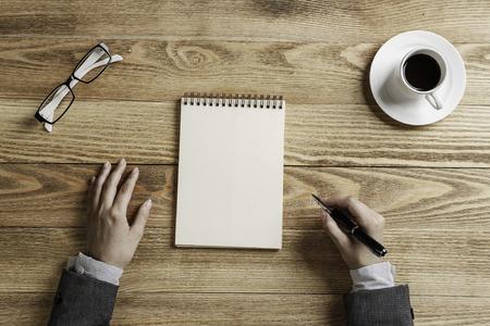 테이블에 앉아 메모장에 메모를 만드는 사업가의 상위 뷰 스톡 콘텐츠