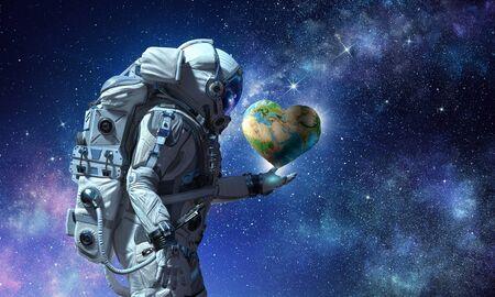 地球の惑星を手のひらに抱く宇宙飛行士。