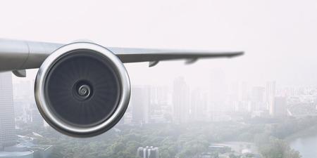 近代的な都市景観の上を飛ぶ飛行機の翼。混合メディア