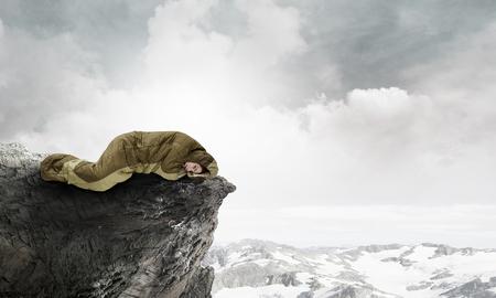 Young woman lying in sleeping bag on rock edge. Mixed media