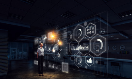 Elegant businesswoman in dark office using virtual panel. Mixed media Standard-Bild