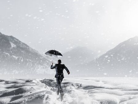 Businessman with black umbrella among snowy mountains ready to overcome any challenge. Mixed media Standard-Bild