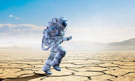 Astronaut man running on desert surface. Mixed media Stock Photo