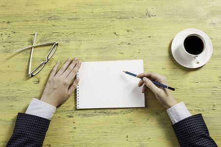 Top view of businesswoman at table with notepad and pen