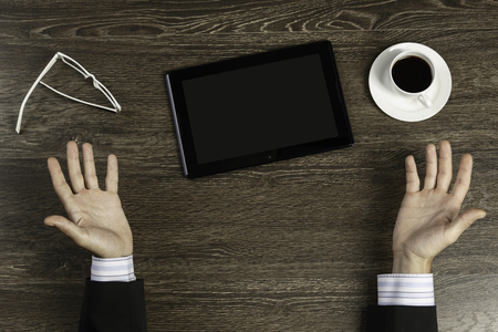 Top view of businessman sitting at table and holding tablet pc Standard-Bild